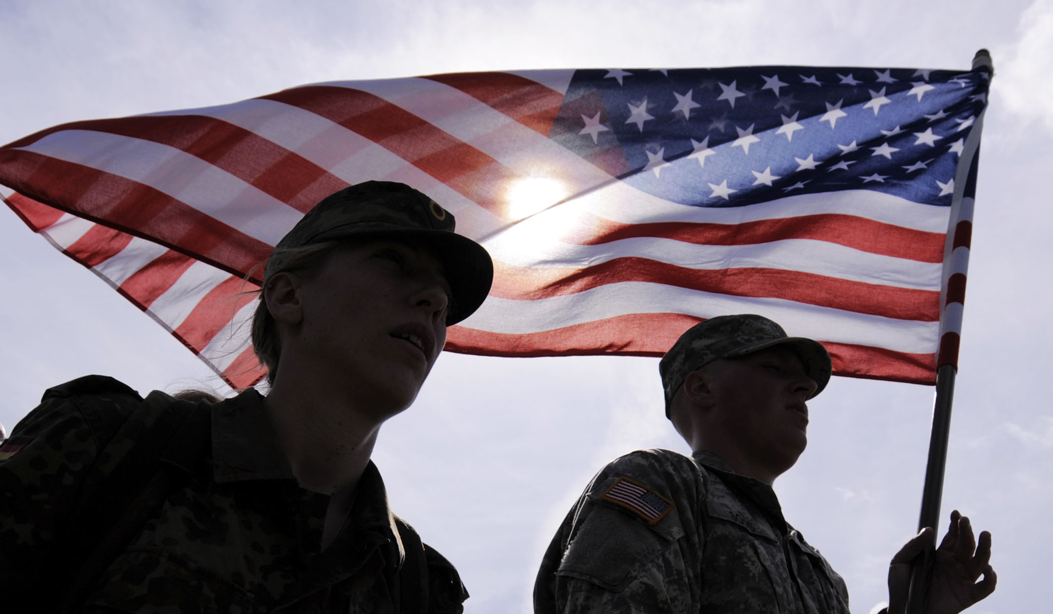 Sergeant Tanja Hoess of German Bundeswehr, left, and Privat Ian Soos of the U.S. Army, right, march with the U.S. flag during the Patrouille – Hlidka – Euregio – Egrensis (PHEE) 2011 International Military Exercise of soldiers from the Armed Forces of the Czech Republic, German Bundeswehr and US Army in Gera, central Germany, on Thursday, June 23, 2011. Some 50 professional soldiers and military reserves will be divided into mixed international teams to fulfil several tasks. (AP Photo/Jens Meyer)